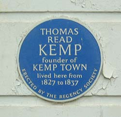 Shows a photograph of a blue plaque with white lettering, commemorating Thomas Read Kemp, who lived in the house. It reads: ' Thomas Read Kemp founder of Kemptown lived here from 1827 to 1837'. Around the bottom, are the words: 'erected by the Regency Society'.