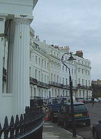 Shows a photograph of Lewes Crescent. In the foreground, to the left, is an ornate column and some railings. The curve of the row of white buildings is evident.