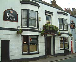 Shows a photograph of a typical old-fashioned British public house. The building is white, and it is decorated with window boxes and hanging baskets.