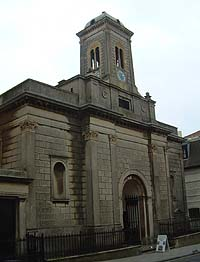 Shows a photograph of St Andrew's Church, a building with a clear Mediterranean influence. It has a clock tower and an arched door.