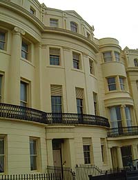 Shows a photograph of the Regency Townhouse. It is a four-storey building painted cream. The first floor has a balcony and columns, ornate mouldings and window blinds decorate the fascia.