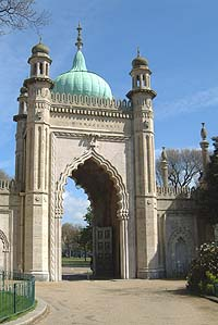 Shows a photograph of a large, ornate stone gateway with an onion-shaped green roof.