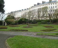 Shows a photograph of Adelaide Crescent. In the foreground is a circular garden display. The background shows a crescent of Regency houses.