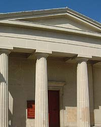 Shows a photograph of the Unitarian Church. The building resembles those of classical Greece. Three of its four pillars are shown, and it has a large red door.